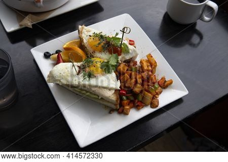 Croque Madame. Bread With Cheese And Sunny Side Up Eggs. Fruits And Potato Home Fries