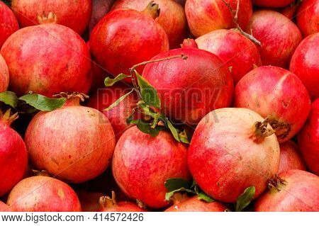 Heap Of Fresh Pomegranates For Sale In Market. Background Of Pomegranate Fruits