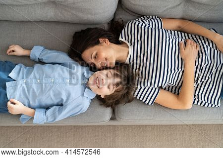 Top Above View Of Happy Young Mom And Little Kid Son Relaxing On Sofa At Home. Couple Of Carefree Mo
