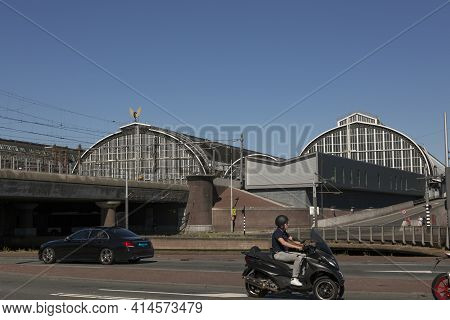 Amsterdam, Netherlands - July 02, 2018: Road With Cars And Motorcycles In Front Of The Amsterdam Tra