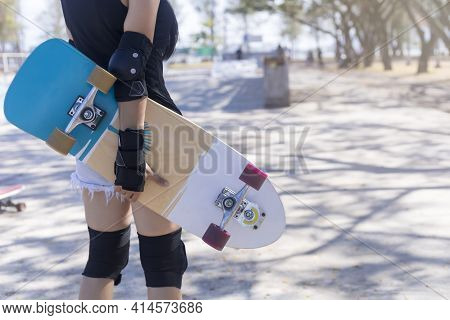 Close Up On Young Women Wear Protection And Hand Hold Skateboard, Surf Skate On Public Skate Ramp Pa