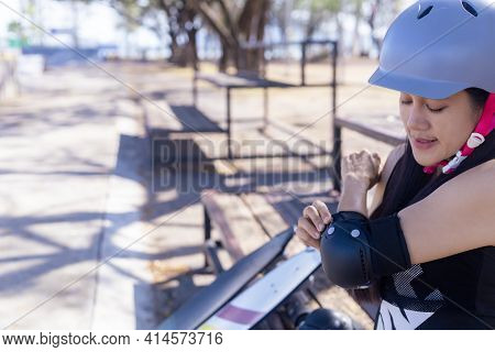 Young Woman Surf Skate Board Putting On Elbow Protector Pads On Her Arm And Wearing Wrist Guards. On