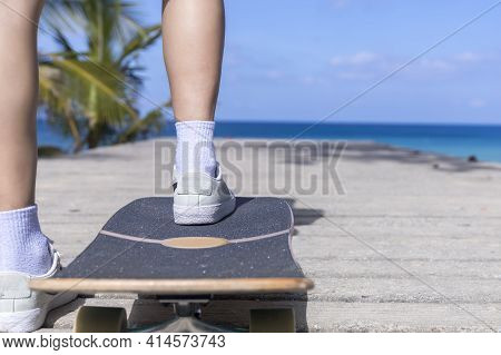 Close Up Young Asian Women Play Surf Skate Board At Beach Road Outdoors On Morning. Happy Women Play