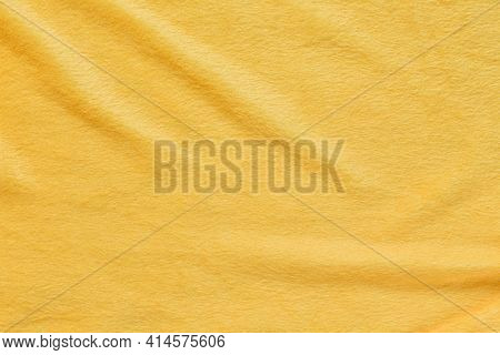 Colored Yellow Textile Satin Fabric Folded In Folds And Waves With Highlights And Texture