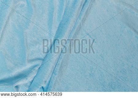 Colored Blue Textile Satin Fabric Folded In Folds And Waves With Highlights And Texture