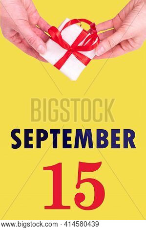 September 15th. Festive Vertical Calendar With Hands Holding White Gift Box With Red Ribbon And Cale