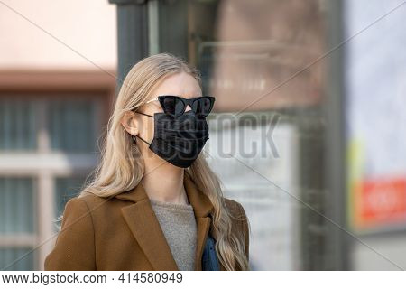 Vilnius, Lithuania - March 28 2021: Beautiful Blond Girl With Mask And Sunglasses Walking In The Cit