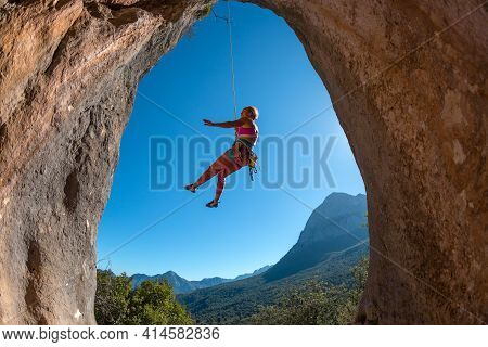 Rock Climber Descends From The Route, The Climber Hangs On A Rope, A Rock In The Form Of An Arch, Cl