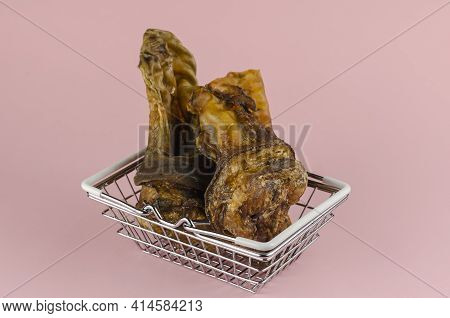 Shopping Basket With Dog Treats On A Pink Background. Chewy Treats In Metal Basket. Dried Beef Ears