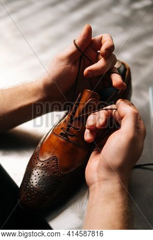 Close-up Top View Of Unrecognizable Male Shoemaker Tying Laces On Repaired And Polished Light Brown