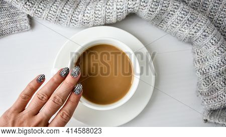 Hand In Sweater With Zebra Animal Printed Nails With Cup Of Cappuccino. Female Manicure. Glamorous B