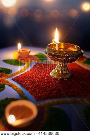 Happy Diwali, Diya Lamps Lit On Colorful Rangoli Against Blurred Bokeh Light Background