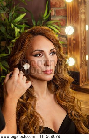 Makeup Preparation Process. Professional Makeup Artist Works With Brush On Model Face In Beauty Stud