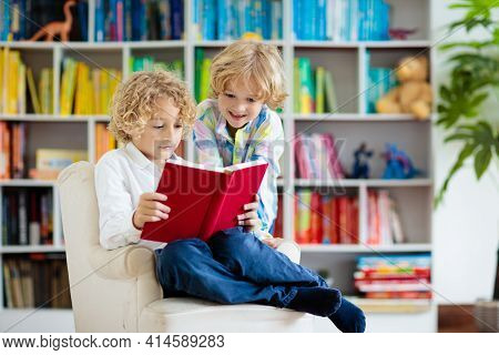 Child Reading Book. Kids Read. Little Boy At A Colorful Bookshelf Doing Homework For School. Student