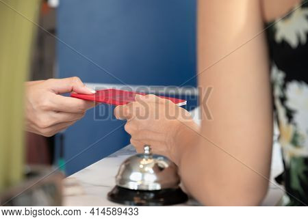 Female Guest Giving Passports To Receptionist At Counter For Hotel Room Registration