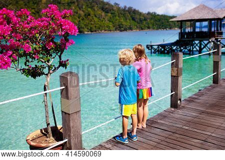 Kids Playing On Tropical Beach. Children Watch Fish And Coral Reef From Luxury Resort Jetty. Travel
