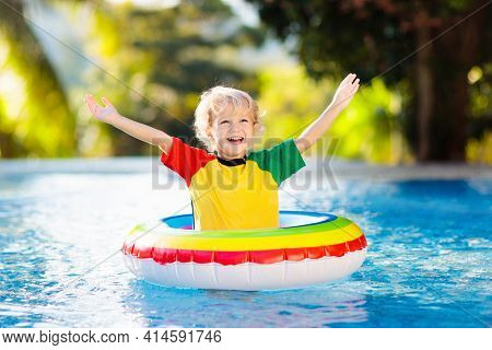 Child In Swimming Pool Floating On Toy Ring. Kids Swim. Colorful Rainbow Float For Young Kids. Littl