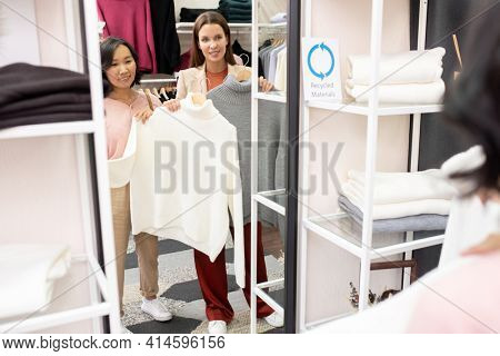 Young woman choosing new jumpers with saleswoman while they standing against the mirror in the shop