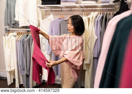 Young woman looking at new beautiful jumper in her hands while buying it in clothes shop