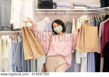 Portrait of happy customer in protective mask holding purchases in her hands standing in clothing store