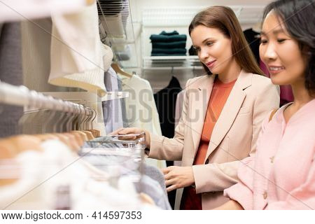 Young Asian woman choosing new clothes for herself with stylist helping her in the store
