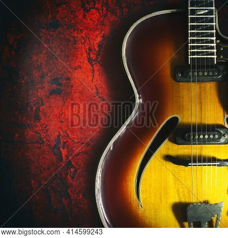 Old, Jazz Electric Guitar On A Red Grunge Background. Copy Space. Close-up. Background For Music Fes