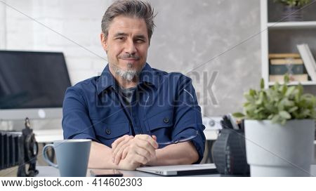 Bearded man working at home sitting at desk. Businessman in home office. Portrait of mature age, middle age, mid adult man in 50s, happy confident smile.