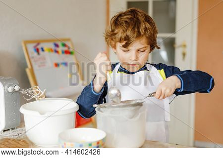 Adorable Funny Blond Little Kid Boy Baking Chocolate Cake And Tasting Dough In Domestic Kitchen, Ind