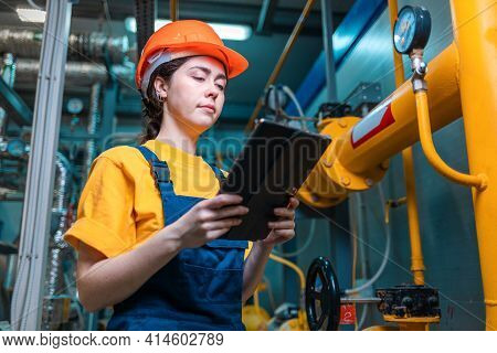 Production Inspection. A Young Engineer In A Uniform And A Protective Helmet, Holding A Tablet In He