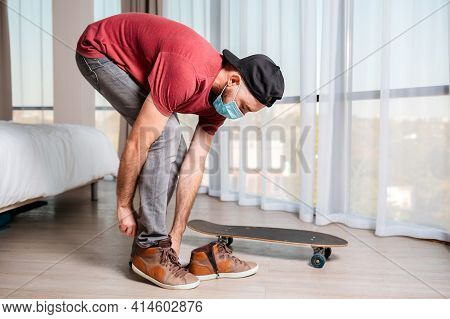 A Young Man In A Medical Mask, Wearing Sneakers Near A Longboard. Indoors. The Concept Of Virus Prot