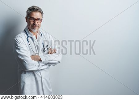 Portrait of trustworthy older smart doctor with gray hair wearing glasses and white lab coat standing against white wall, smiling. Copy space.