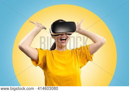 A Young Happy Woman In Virtual Reality Glasses, In Amazement, Stretches Out Her Hands In Different D