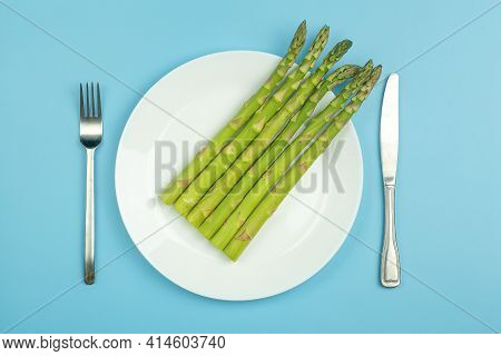 Asparagus On A White Plate On A Blue Background. Fresh Vegetable Asparagus For A Healthy Diet And Nu