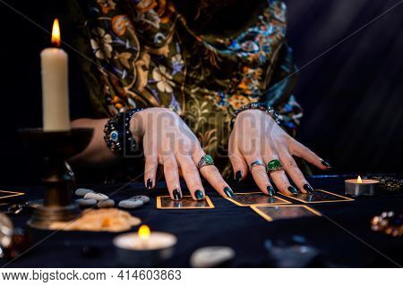 A Fortune Teller Reads Tarot Cards. On The Table Are Candles And Fortune-telling Objects. Hands Clos
