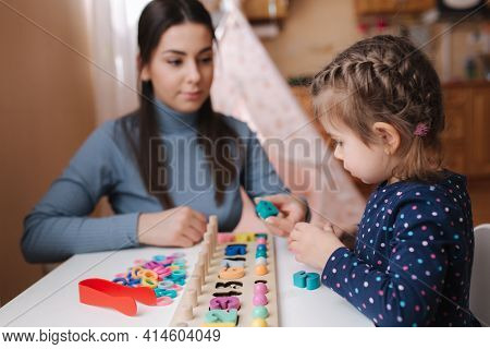 Little Girl Play In Educational Game For Children With Mom. Wooden Game With Different Colors And Nu