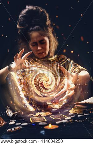 Portrait Of An Elderly Witch Conjuring A Magic Energy Ball With Her Hands. The Concept Of Astrology,