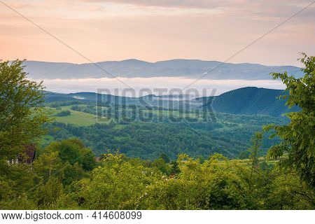 Mountainous Rural Landscape At Sunrise In Summer. Fog In The Distant Valley. Green Plants And Trees