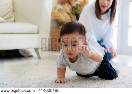 Asian Baby Crawl With Determination. Mother Looks At The Child's Development With Pride. Her Face Is