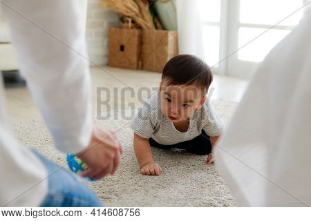 Asian Baby Crawl Towards Their Parents. His Face Is Smiling.happy Family Time
