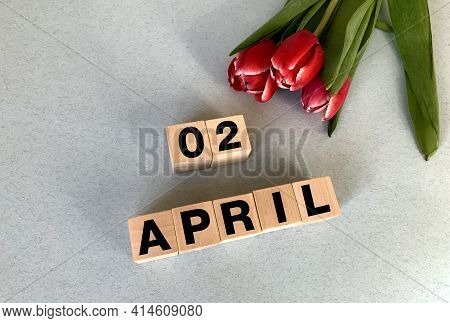 April 2 On Cubes Of Wood On A Gray-blue Background.spring.calendar For April.