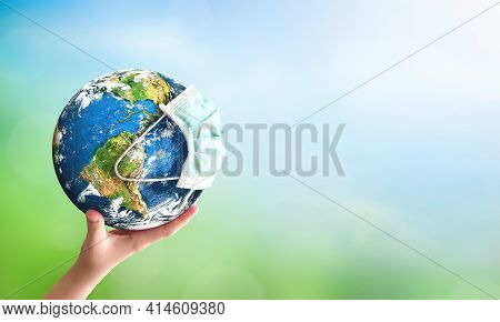 Earth Day Concept: Human Hand Holding Earth Globe Over Blurred Green And Blue Nature Background. Ele