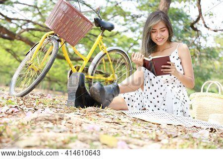 An Asian Girl Enjoying Reading In The Garden. A Female Office Worker Enjoying Time Away From Technol