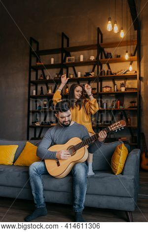 Young Couple Playing Guitar On Sofa At Home. Bearded Man Plays Guitar For Woman. Woman Dancing While