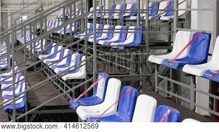White And Blue Plastic Seats Without Spectators In A Sports Stadium With Red Prohibition Ribbons Str