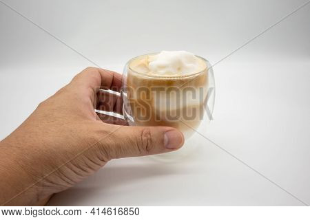 Hand Holding Coconut Blend Coffee In Double Wall Glass Isolated On White Background.