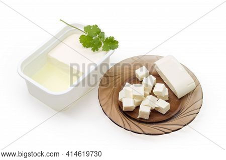 Fresh Feta Cheese Partly Diced On Glass Saucer And The Rest Cheese Soaked In Whey In Container On A