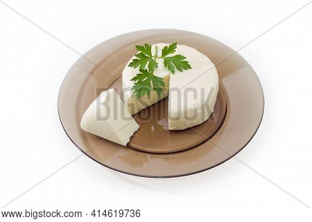 Ball Of Fresh Mozzarella Cheese Partly Cut, That Was Soaked In Whey, Decorated With Parsley Twig On