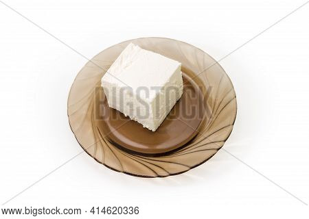 Piece Of Fresh Feta Cheese, That Was Soaked In Whey On A Dark Glass Saucer On White Background