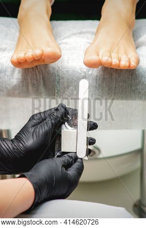Nail File Tool In Hands Of Chiropodist Before Procedure Files Nails On Toes In A Nail Salon