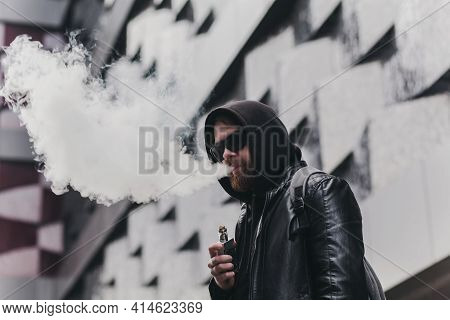 Vaping Man Holding A Mod. A Cloud Of Vapor. Stylish Bearded Guy With Vape.